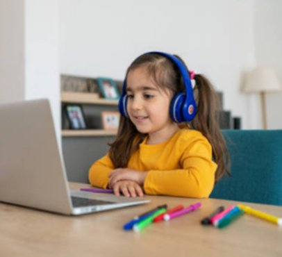 girl sitting at a desk with headphones on and looking at a laptop with markers on the desk next to her