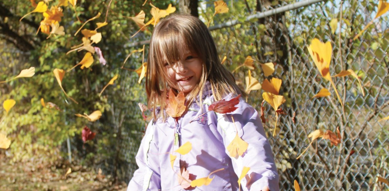 girl in jacket outside with leaves falling around her